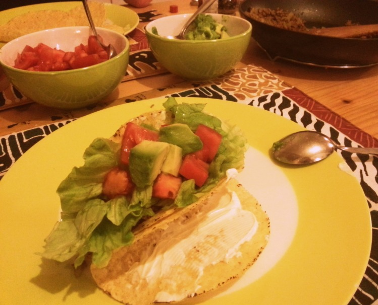Tacos with ground beef, tomato, lettuce, avocado and sour cream.
